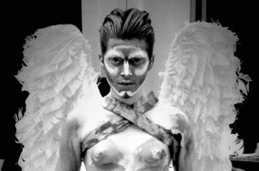 A man covered in white paint, wearing a pair of white wings stares directly into the lens.