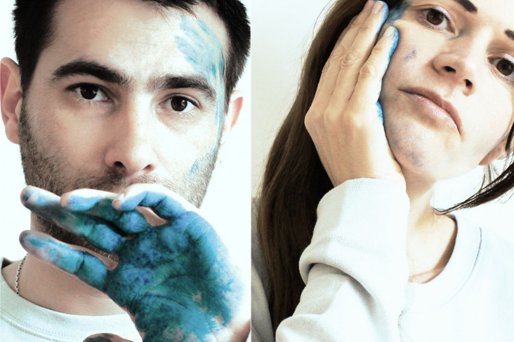 Featured News Post A man and a woman with blue paint on their hands, smudge the paint against their faces.