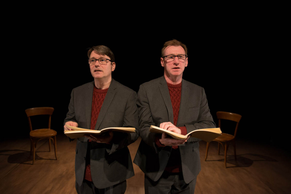 Two men both dressed in grey suits, wearing red jumpers are stood facing the audience holding brown books.