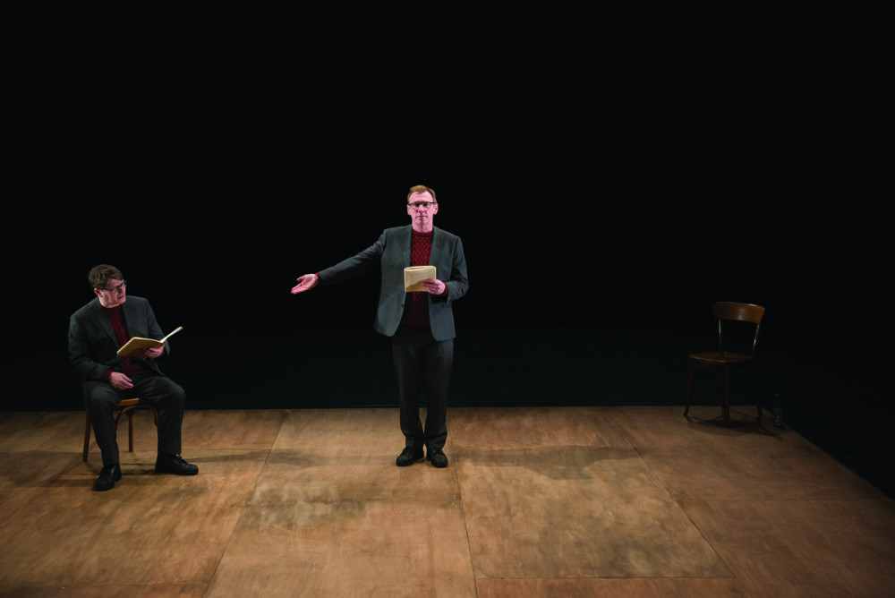Two men both dressed in grey suits, are wearing red jumpers. One is stood facing the audience, holding his hand out to the other man who is sat on a chair, they are both holding brown books.