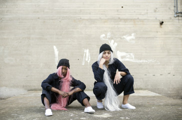 Two girls crouch down wearing overalls and long wigs under beanie hats