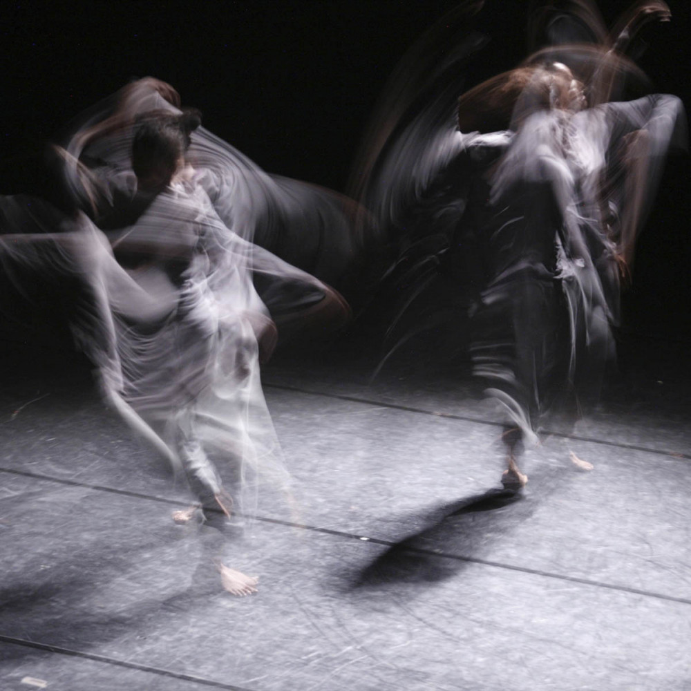 Two figures dressed in grey dance, the image is blurred by the slow shutter release.
