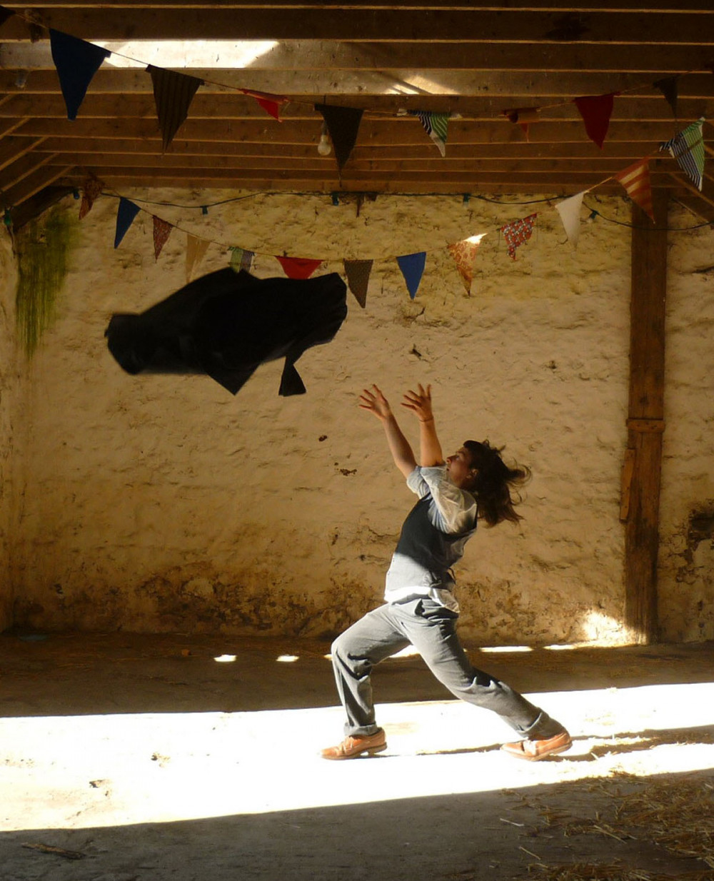 A woman dressed in a suit, is standing in a barn, she has thrown her jacket into the air and is about to catch it.
