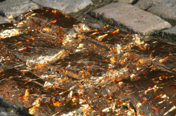 Copper plastic is broken across pavement slabs.