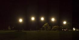 Five flood lights light up a green field at night.