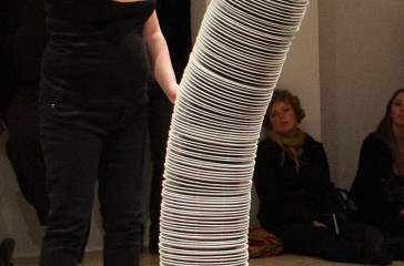 A woman stands facing a six foot stack of plates.