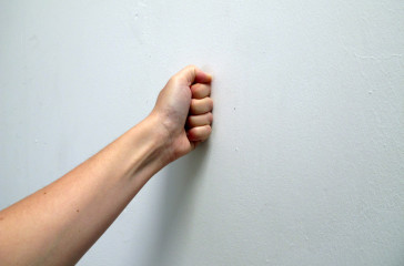 A fist is pressed up against a white wall.
