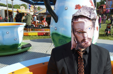 Man sits on fairground ride wearing a mask with an image of a face on it