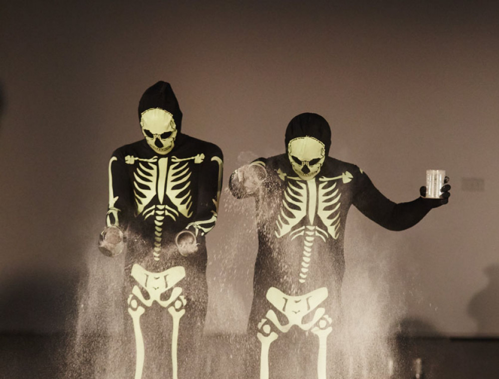 Two figures dressed in black and white skeleton suits.