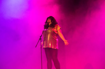 A female figure dressed in gold sings into a microphone there is pink smoke in the background