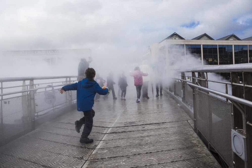 Children run across a bridge surrounded by fog.