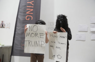 Two children are wearing gorilla masks and are holding signs that read 'no more trump' and 'more money for schools and nhs'