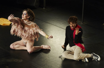 Two figures sit on the floor, one dressed in feathers the other dressed in plain clothing and a red scarf.