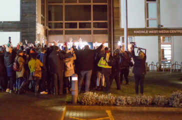 A large huddle of people stand with their backs to us and their arms raised outside knowle west media centre