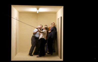 A group of 7 people huddle in the corner of a film set which looks like a neutral room. They all lean back and hold on to a rope which leads off camera