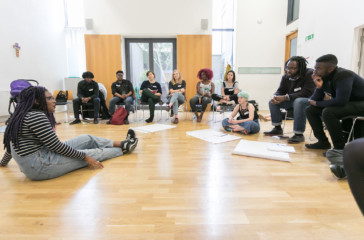 A women sits on the floor speaking to a group who sit in a semi circle around her.