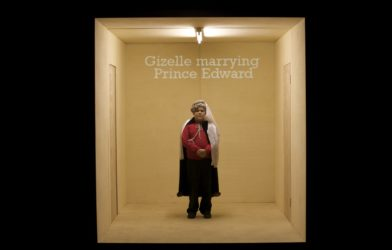 A boy stands in an empty room. He wears a medieval looking headpiece. On the back wall the words 'Gizelle marrying Prince Edward' are projected.