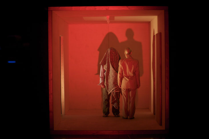 Featured News Post Two figures stand in a wooden box which is lit up with red light, their shadows are cast ont he wall and we can't see their faces