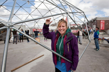 Kirstin Shirling holds up a section of a geodome which is being put together