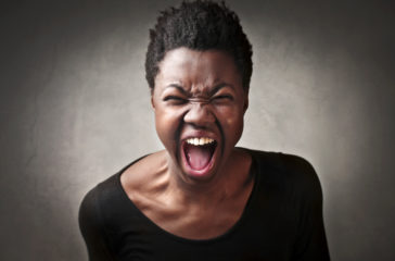 A woman roaring with her mouth open