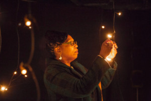 Woman looking closely at a light hung from a string in a dark room