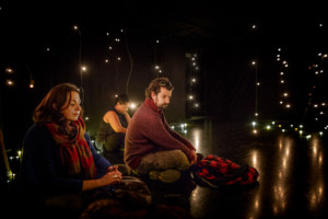 Three people sit cross legged on the floor of a dark room. They are surrounded by hanging lightbulbs. The light reflects on the shiny black floor.