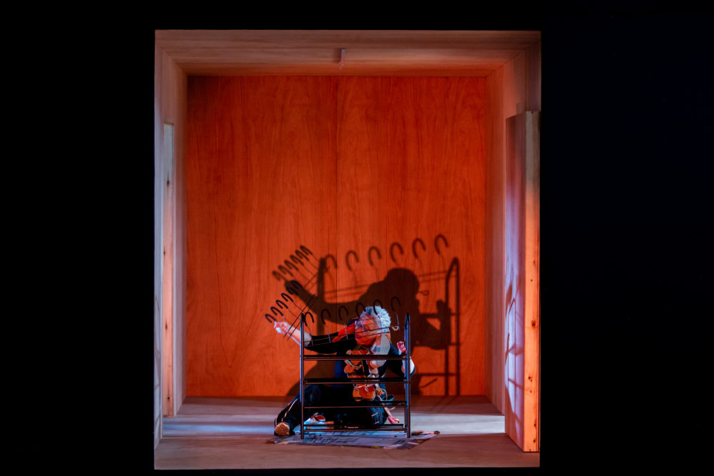A woman sits on the ground constructing a shoe rack. She is lit from the front with red lighting and cast a dark shadow on the wall behind her.