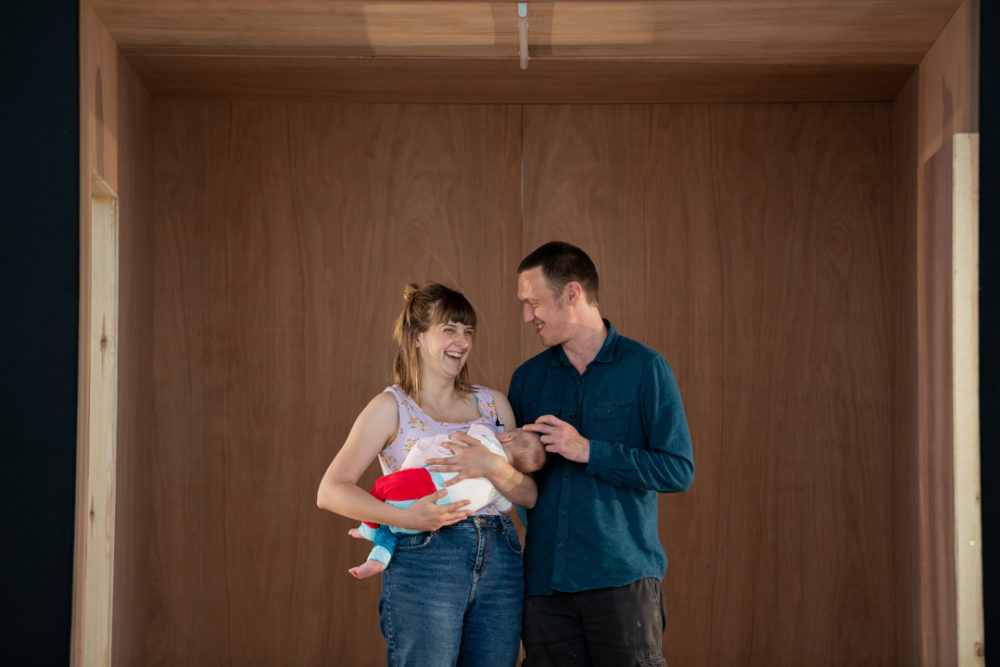 A young woman and a man look at each other laughing. She holds a baby to her chest. He is stroking the babies head.