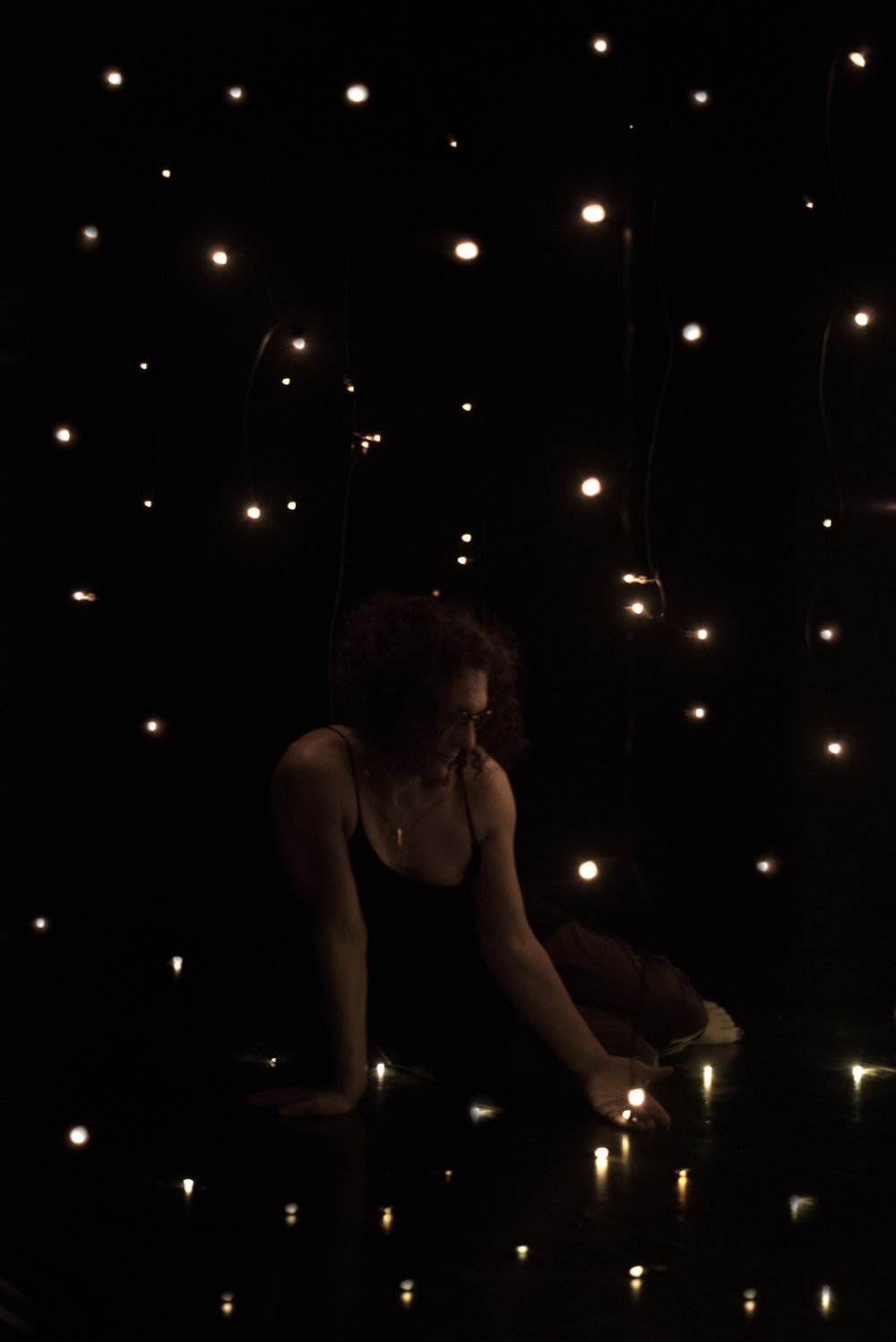 A woman sits in dark room surrounded by tiny lights. She holds one of the lights in an open hand.