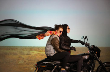 Two women riding on a motorbike in a desert landscape with a long scarf flowing behind them
