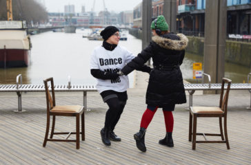 Two people dancing outside by the waterfront