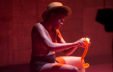 A woman in shorts and a straw hat peels oranges on a stage