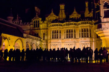 A wide shot of Tynsfield Manor house lit up at night