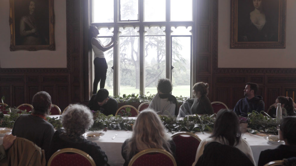 A performer stands of a windowsill inside Ashton Court Mansion. An audience seated at a long dining table watch.