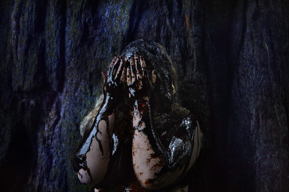 Charneh Watson, Creative Exchange Lab artist with hands over her faced covered in black liquid