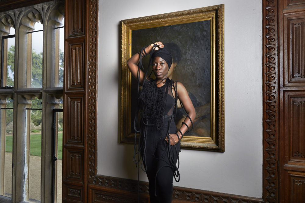 Julene Robinson, Creative Exchange Lab artist standing in front of a portrait at Arts Mansion
