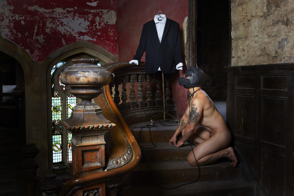 Kelvin Atmadibrata, Creative Exchange Lab artist kneeling wearing only a black dog mask next to a mans suit on a staircase
