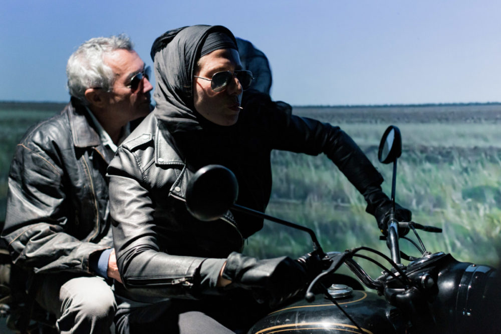 A woman in a headscarf rides a motorbike, a man with grey hair sits on the back