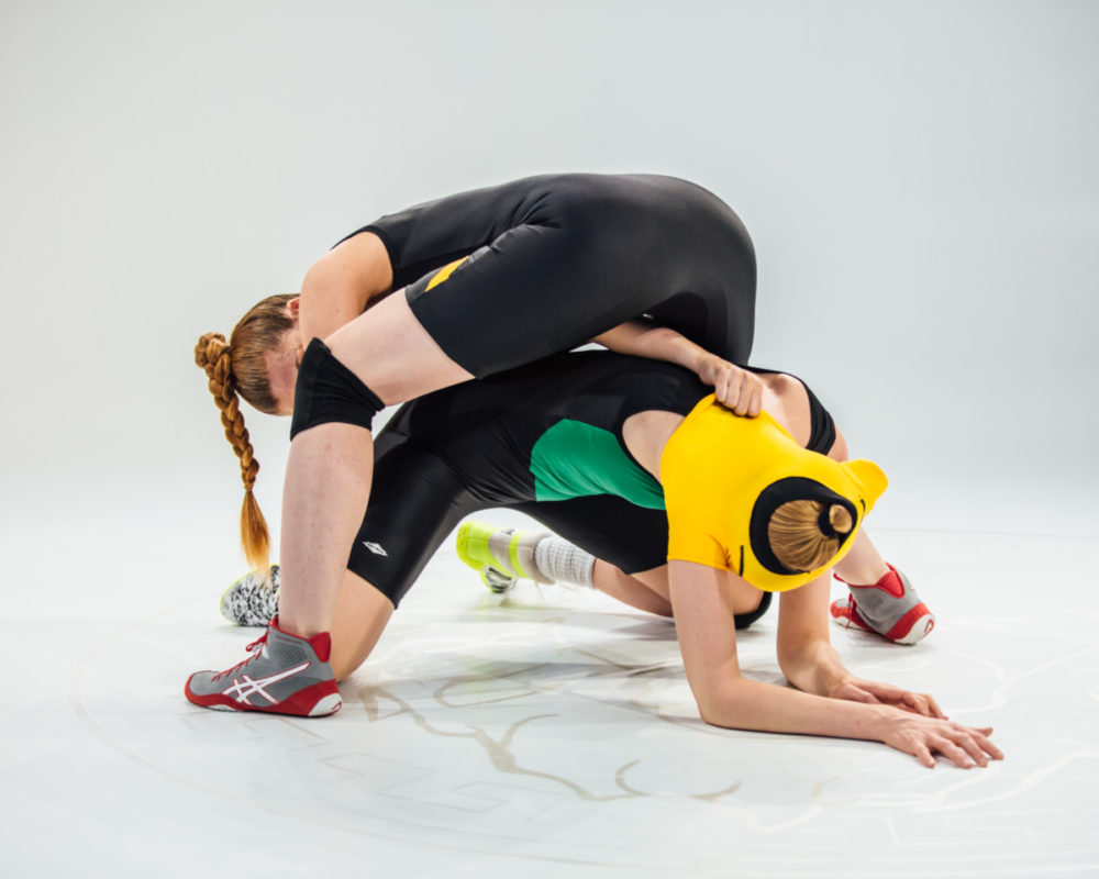 A photo from Erin Markey's show Singlet. A women wearing a wrestling singlet crouches over another woman wearing a wrestling singlet